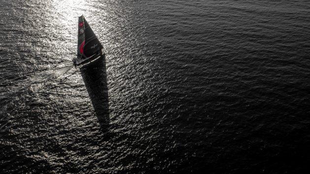 A yacht at full sail at dusk