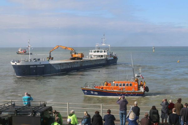 A cargo ship aground off Margate with an orange RNLI lifeboat providing safety cover