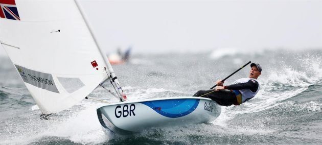 Dressed in black, Nick Thompson leans out in his laser, which has a white sail