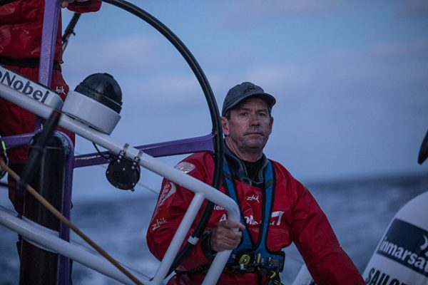 Brad Jackson wearing red wet weather gear at the helm