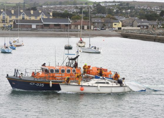 An orange all weather lifeboat assists a dismasted yacht at Wicklow