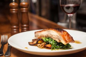 A glass of red wine with a dish of pork belly and vegetables.