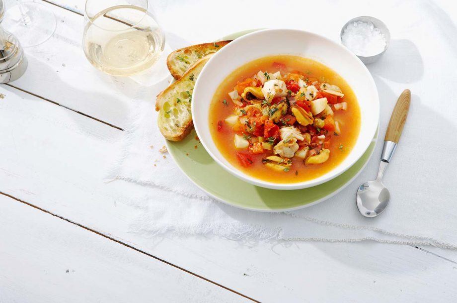 A bowl of bouillabaisse with bread and a glass of white wine