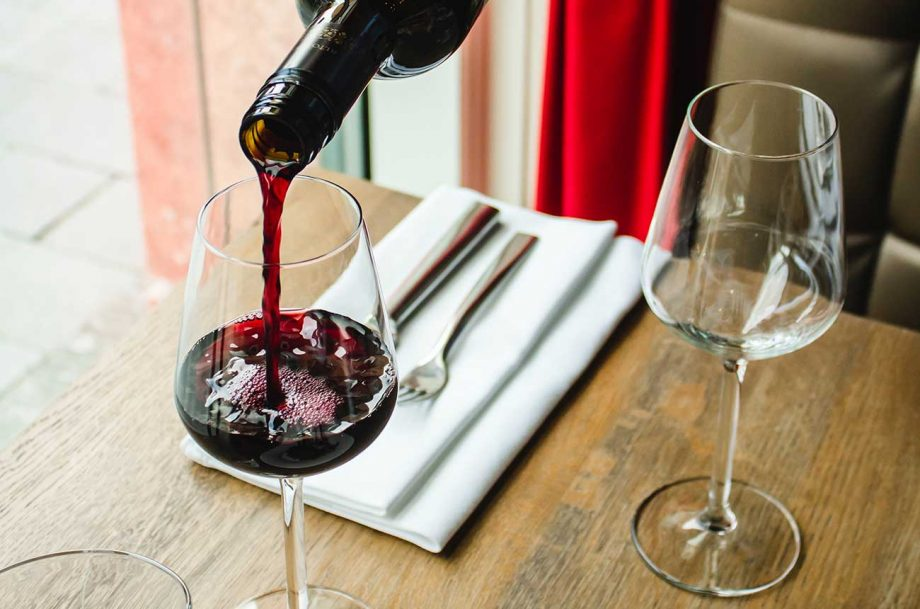 A glass of red wine being poured at a restaurant