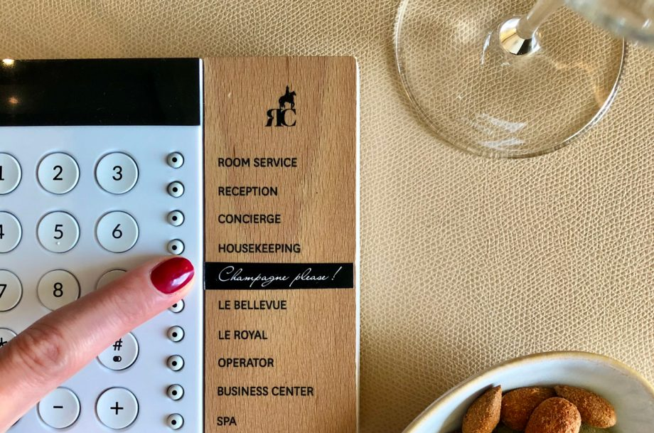 A finger presses a button for Champagne Please in a hotel suite call system