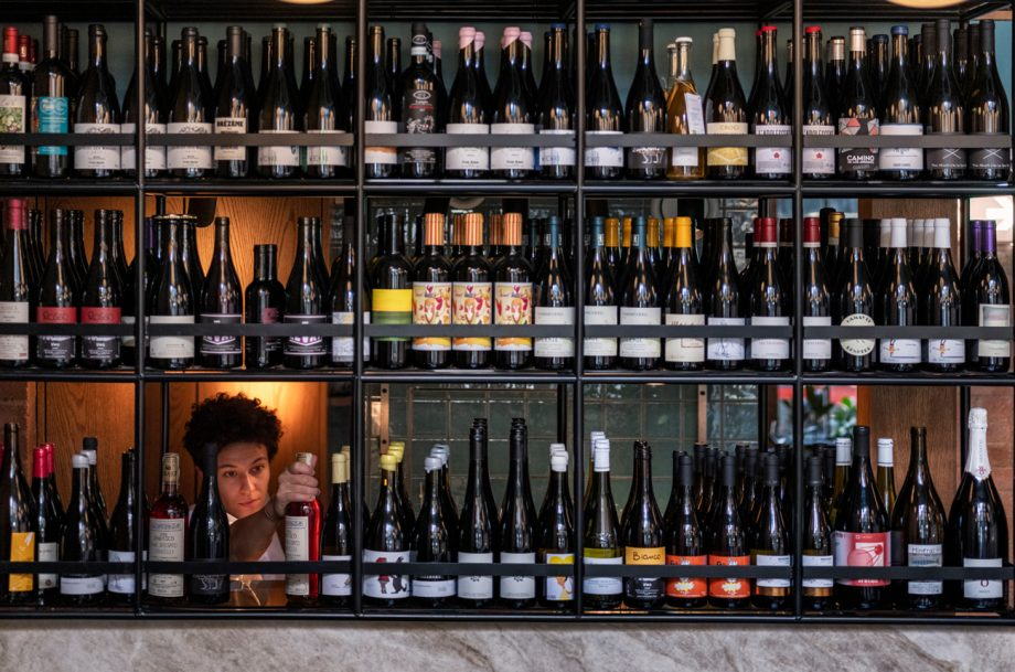 The wine wall at Flor with a sommelier selecting a bottle