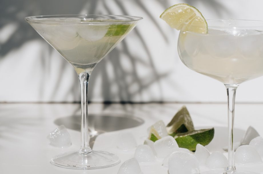 Two margarita cocktails in cocktail glasses with a palm leaf shadow behind