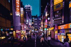 Tokyo street at night with neon signs and people walking