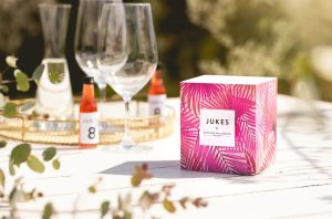 Wine glasses and a box of Jukes Cordials on a summery table