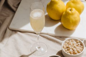 Glass of wine on a table with lemons and a bowl of white currants