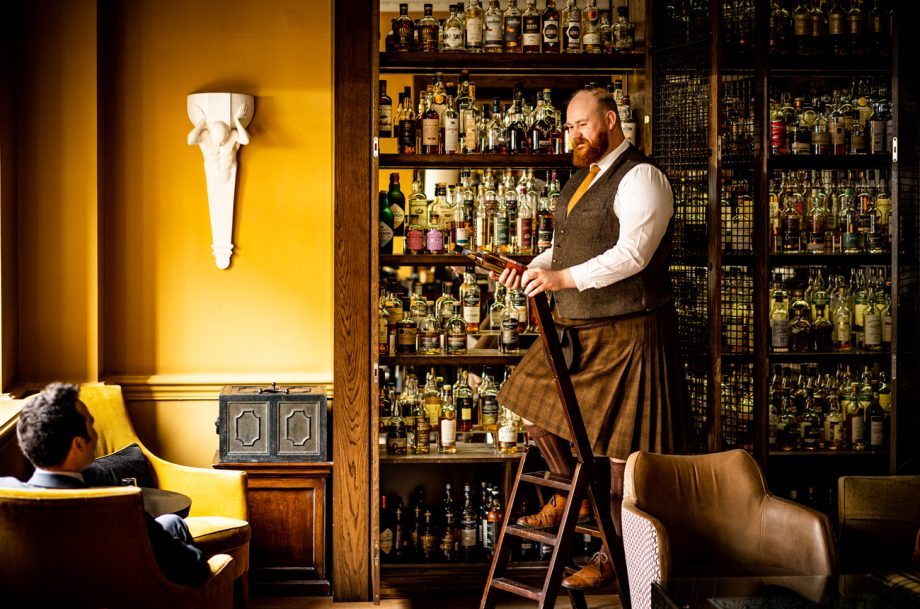 A kilted man fetches a bottle of whisky for a guest at Scotch bar at The Balmoral hotel