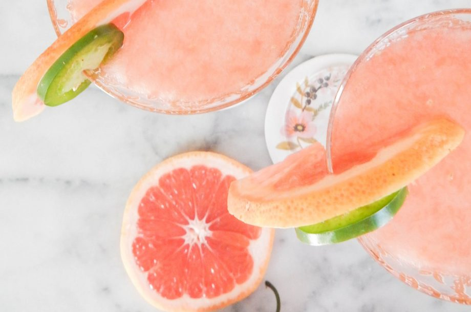 Two pink Paloma cocktails with slices of grapefruit and lime
