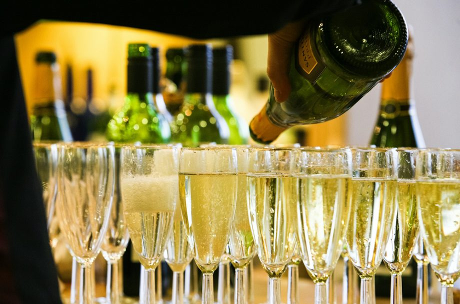 A person pouring from a bottle of sparkling wine into glasses on a bar top best cava under £25