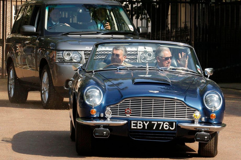 Prince Charles being driven in his Aston Martin, which runs on fuel partly made from wine leftovers.