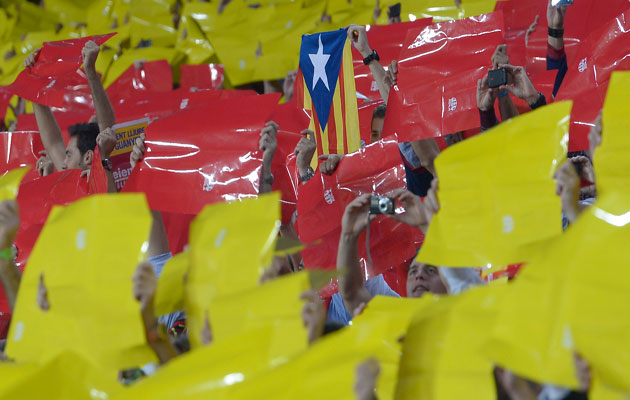 "Barcelona fans hold up 'Estelada', the Catalan independence flag, amongst color cards forming the red-and-yellow stripes of Catalonia's ""la senyera"" flag"