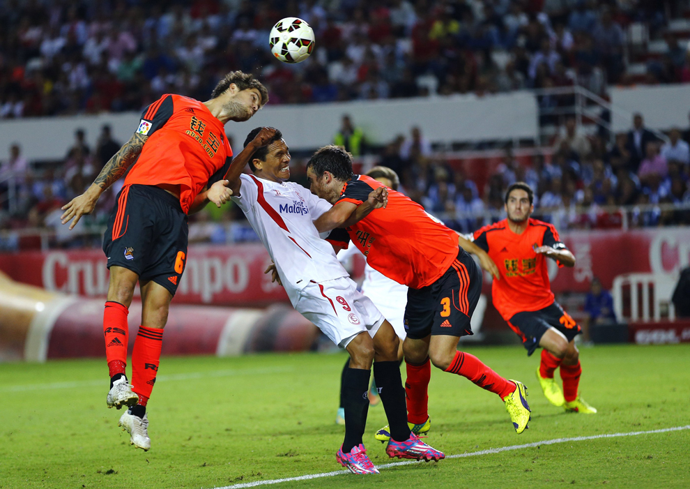 Sevilla's Carlos Bacca is challenged by Real Sociedad's Inigo Martinez and Mikel Gonzalez during their soccer match in Seville