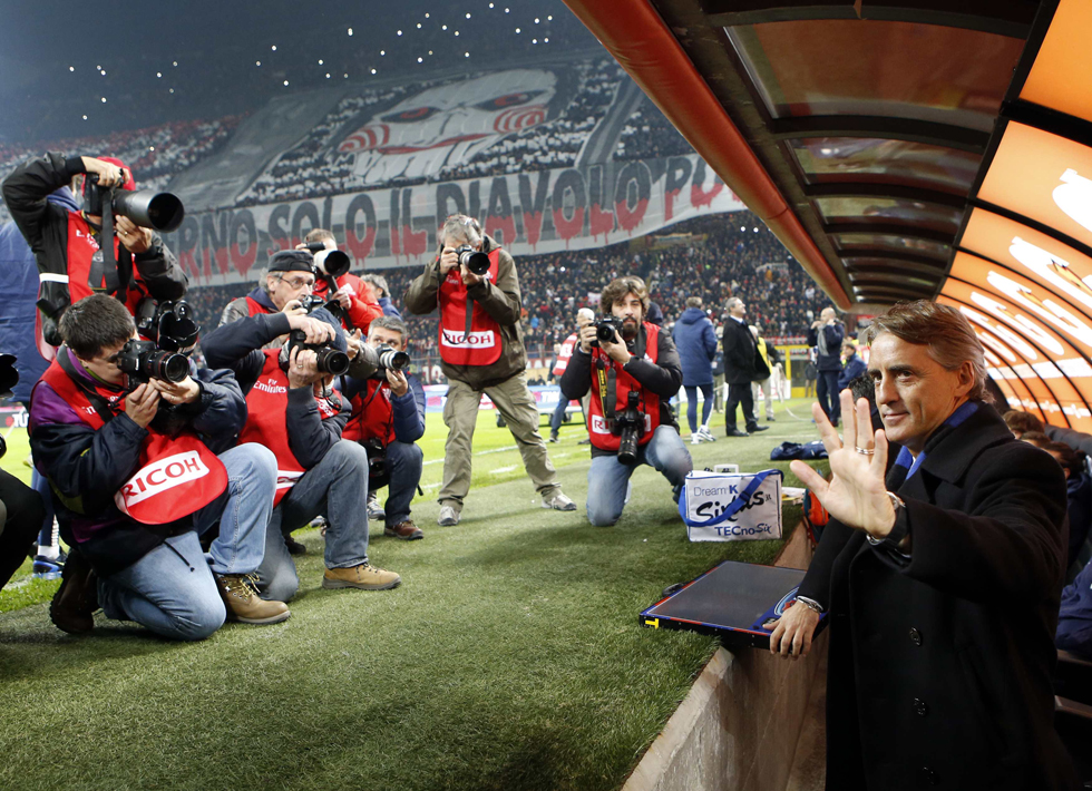 Inter Milan's coach Mancini waves to photographers before the start of their Italian Serie A soccer match against AC Milan in Milan