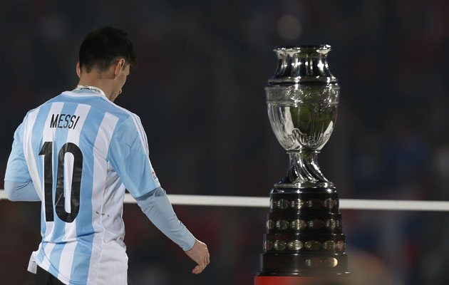 A forlorn Lionel Messi walks past the Copa America trophy.