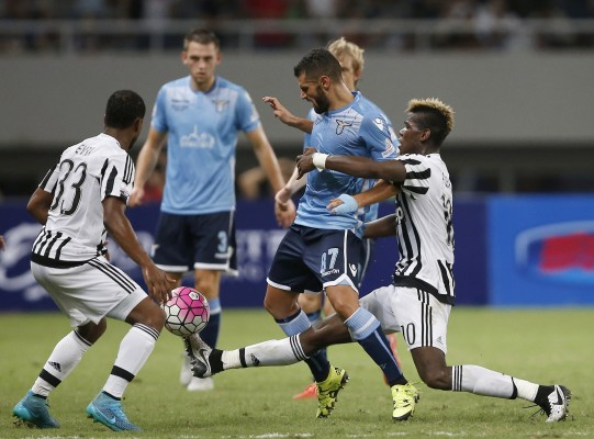 Juventus' Labile Pogba fights for the ball against Lazio's Candreva during their Italian Super Cup soccer match in Shanghai