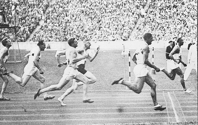 Jesse Owens wins the 100m gold medal at the 1936 Olympic Games.