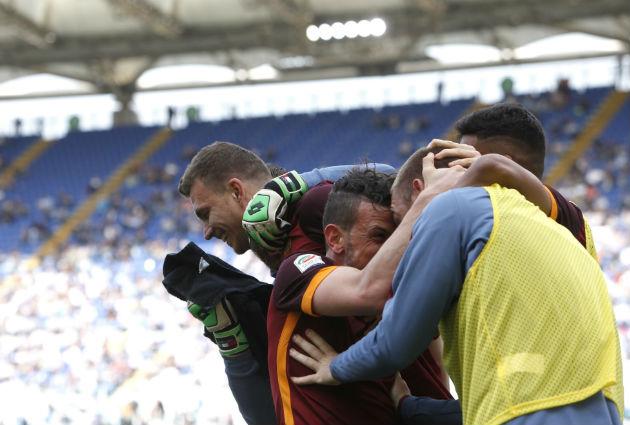 Edin Dzeko, left, celebrates with teammates after scoring during match between Lazio and Roma