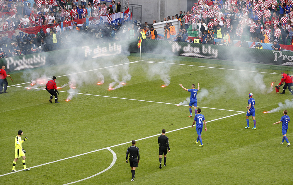 Stewards tend to flares that have been thrown onto the pitch by Croatia fans as players look on.