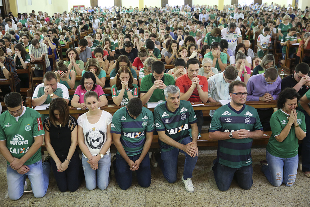 Supporters of Brazil's soccer team Chapecoense attend Mass at the city's Cathedral in Chapeco, Brazil, Tuesday, Nov. 29, 2016. A chartered plane carrying the Brazilian soccer team Chapecoense to the biggest match of its history crashed into a Colombian hillside and broke into pieces, killing most passengers, Colombian officials said Tuesday. (AP Photo/Andre Penner)