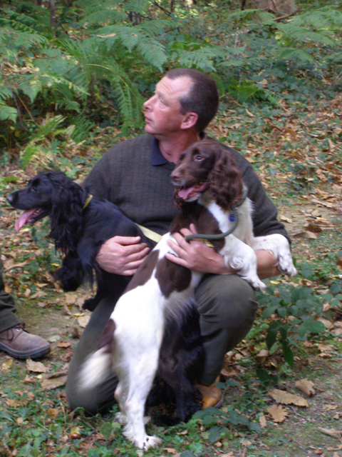 Guy waiting at field trial with his two spaniels.