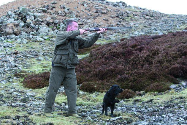man shooting over dog