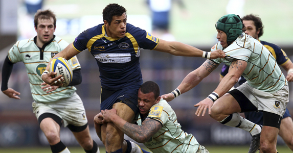 Luther Burrell (c) is tackled by Courtney Lawes of Northampton Saints