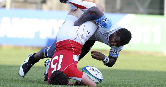 Ross Jones of Walles is tackled by Solomoni Rosolea of Fiji