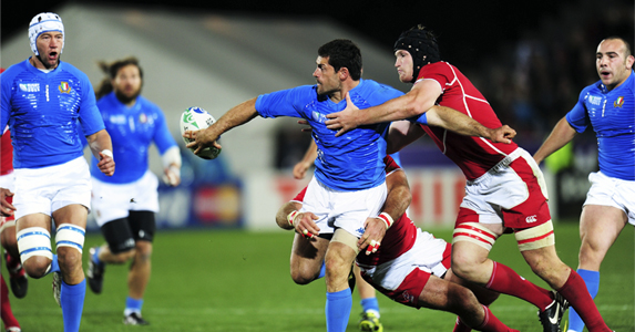 Andrea Masi of Italy (C) offloads the ball as he is tackled by Vyacheslav Grachev of Russia
