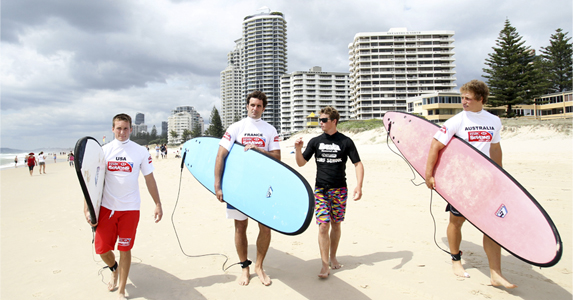 (L-R) Peter Tiberio of USA, Jean Baptiste Gobelet of France and Jesse Parahi of Australia walk with surfboards at Surfers Paradise beach ahead of the IRB HSBC Sevens World Series