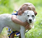 young child cuddles her dog