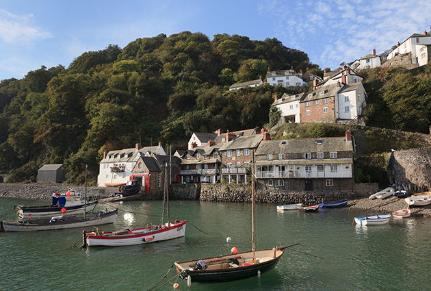 North Devon property, England, UK. Coastal scene with boats in the harbour below the village on a steep hillside