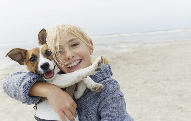 Happy girl hugging dog on the beach, portrait