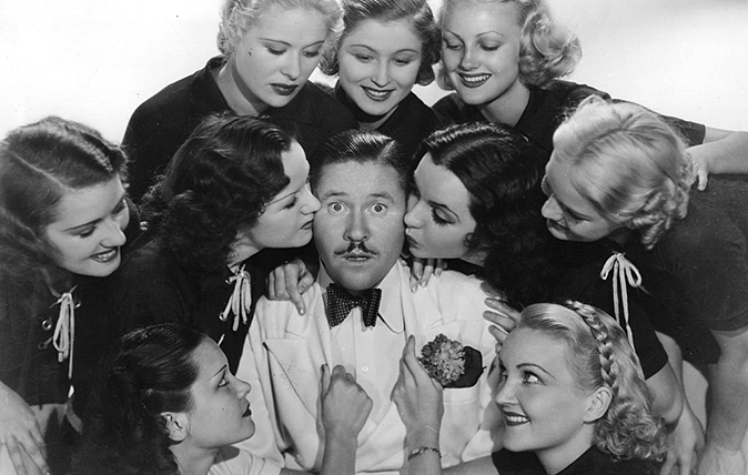 Awkward kissing: Bemused American comic actor Jack Oakie (1903 - 1978) surrounded by a bunch of lovelies in the 1936 Paramount film 'Collegiate' (UK Title: 'Charm School'), directed by Ralph Murphy.