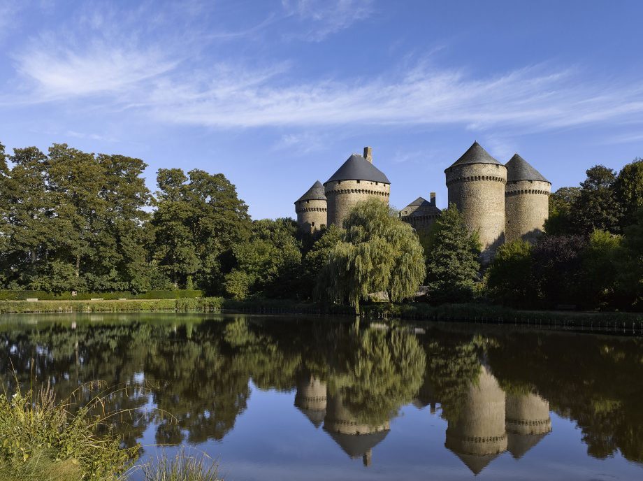 View of Château des Lassay in Mayenne, France, standing on a rock, above a pool.
