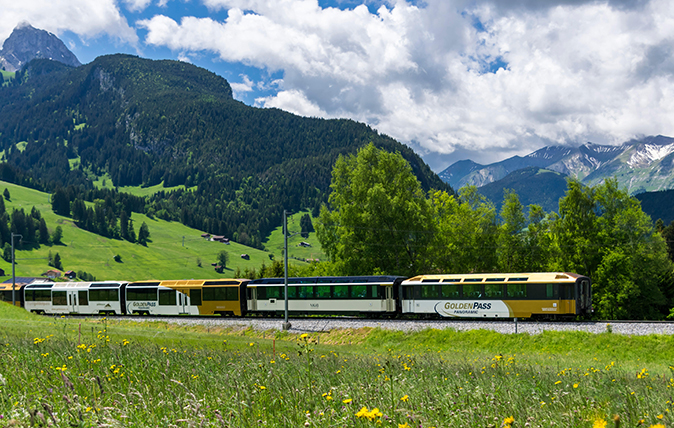 Panoramic train of the MOB Montreux-Oberland Bernois railway on the GoldenPass line close to Gstaad, Switzerland