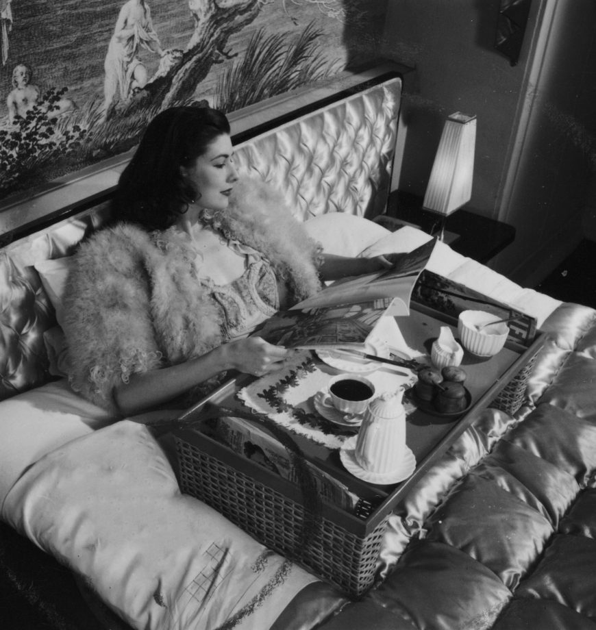 Photograph by Zoltan Glass of a model wearing a mohair or feather bed jacket, reading a magazine, with her morning coffee on a tray.