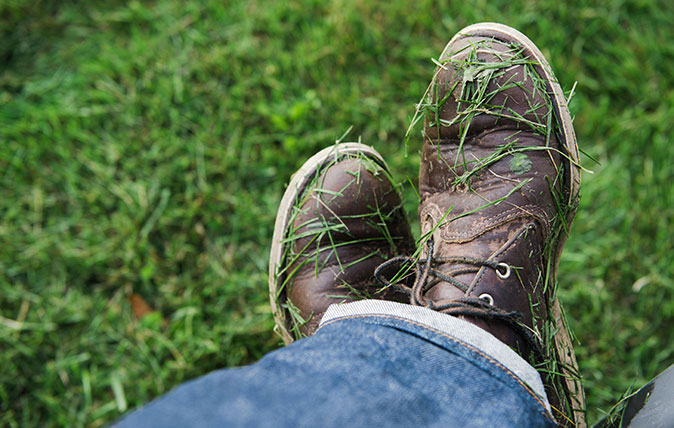 Man's shoes covered in freshly mown grass
