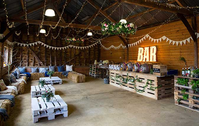Party Barn decorated for social event, with bunting, string lights and illuminated bar sign