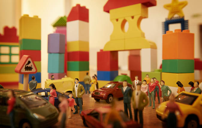 Toy cars and figurines in pretend plastic block town