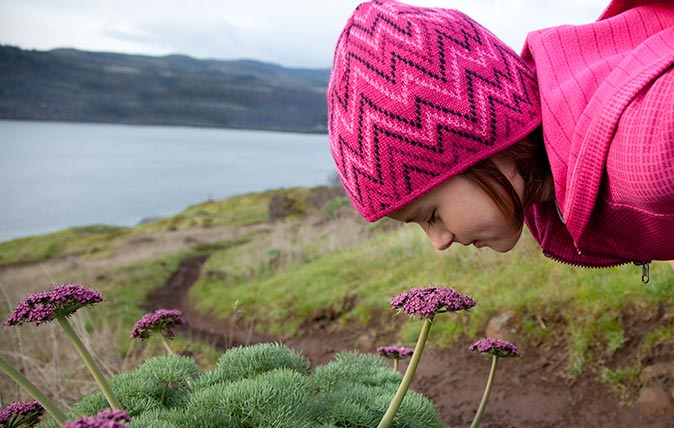 A young girl dressed in pink smells the spring flowers, while out hiking.
