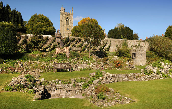 The ruins of Shaftesbury Abbey Dorset UK with a statue of King Alfred and the shrine which once housed the relics believed to be