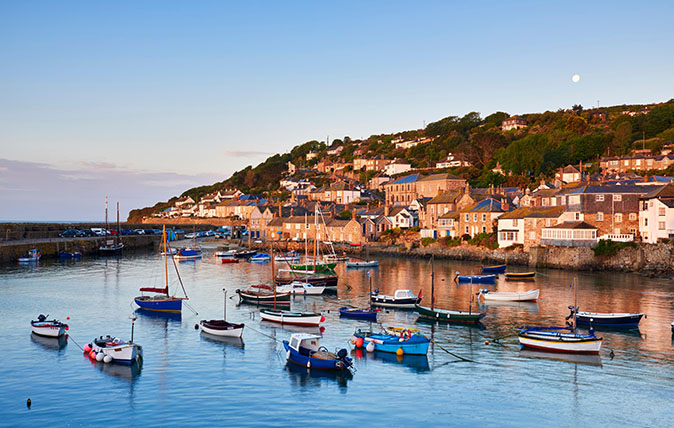 The first light of dawn catching the cottages along the waterfront, overlooking the picturesque Cornish harbour of Mousehole.