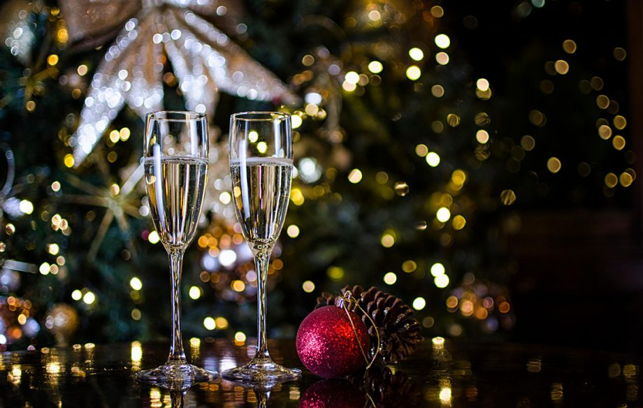 Two Champagne Glasses surrounded by Christmas Decorations