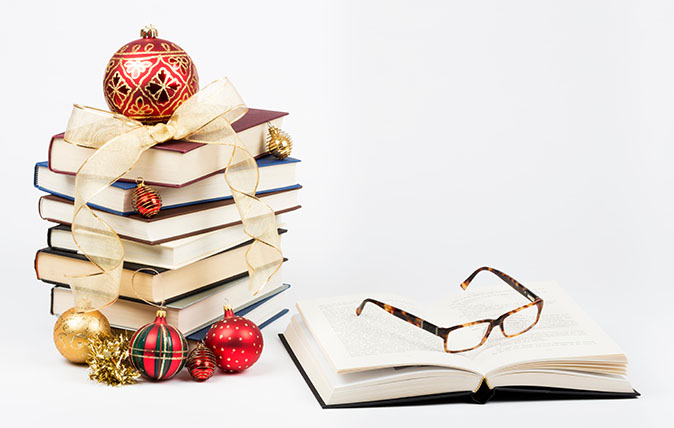 Gift of knowledge concept with a pile of books and reading glasses with Christmas ornaments