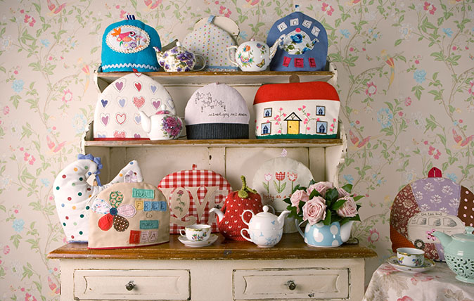 A collection of Tea Cosies on a Welsh Dresser