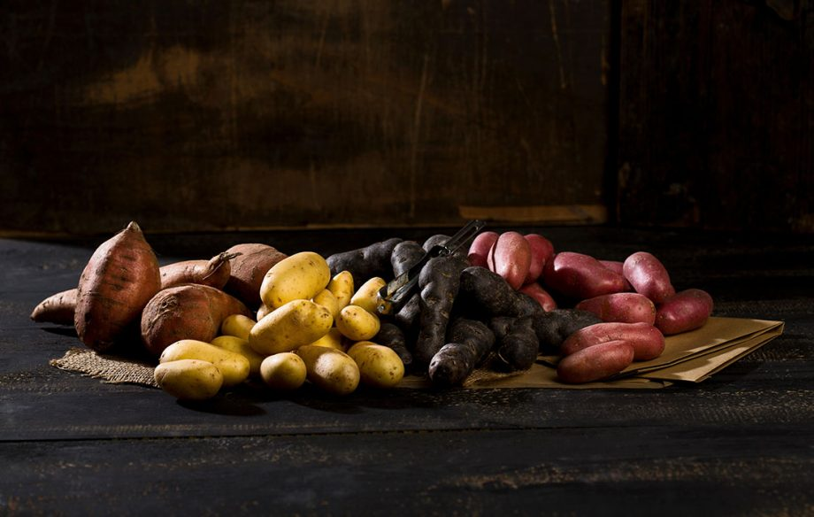 Different sorts of potatoes on brown paper, jute and dark wood